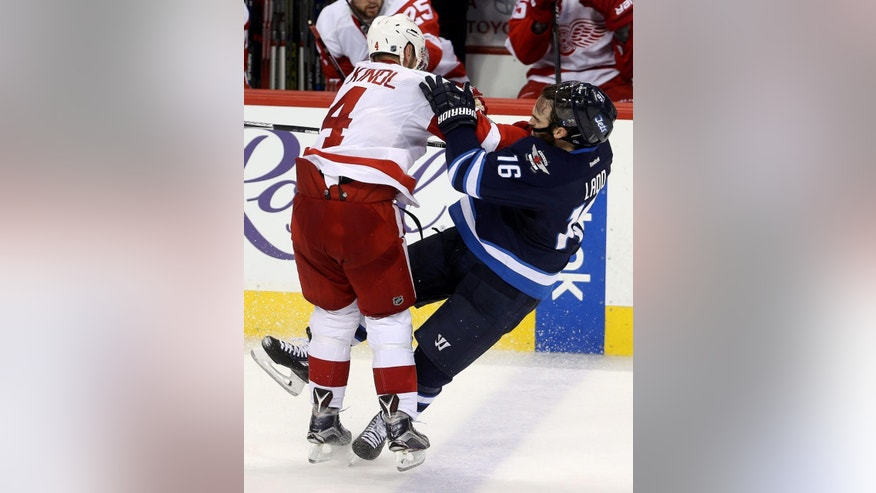 Detroit Red Wings' Jakub Kindl (4) hits Winnipeg Jets' Andrew Ladd (16) during the third period of an NHL hockey game Tuesday, Dec. 29, 2015, in Winnipeg, Manitoba. (Trevor Hagan/The Canadian Press via AP)