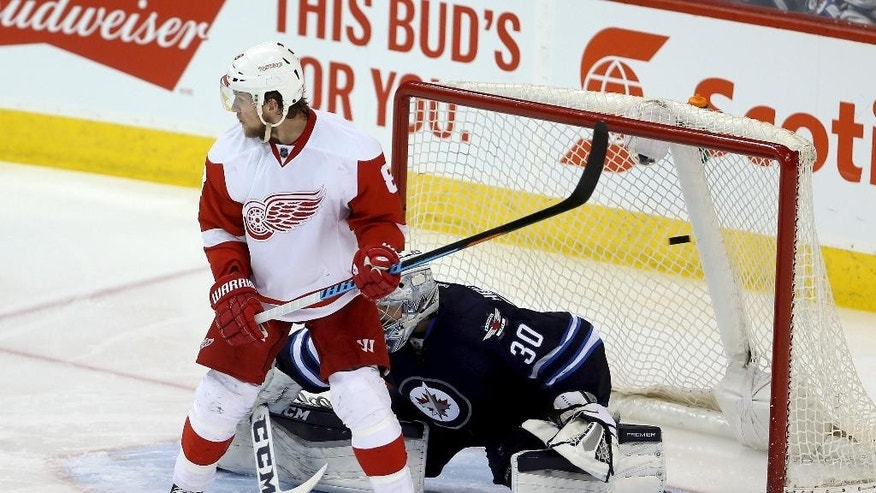 Detroit Red Wings' Justin Abdelkader (8) screens Winnipeg Jets goalie Connor Hellebuyck (30) as Pavel Datsyuk (13) scores during the third period of an NHL hockey game Tuesday, Dec. 29, 2015, in Winnipeg, Manitoba. (Trevor Hagan/The Canadian Press via AP)