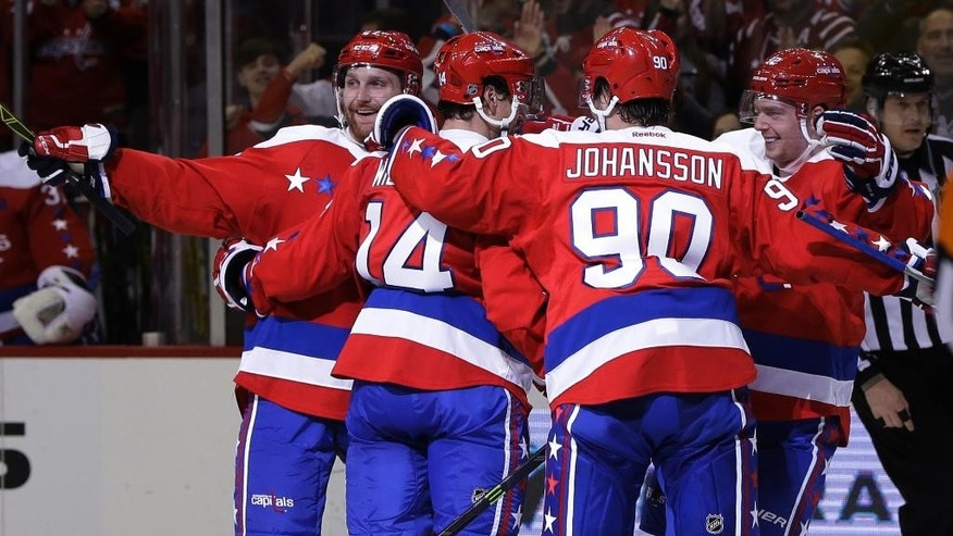 Washington Capitals right wing Justin Williams (14) celebrates his goal with teammates Marcus Johansson (90), Karl Alzner (27), and  Evgeny Kuznetsov (92) during the second period of an NHL hockey game against the Buffalo Sabres, Wednesday, Dec. 30, 2015, in Washington. (AP Photo/Carolyn Kaster)