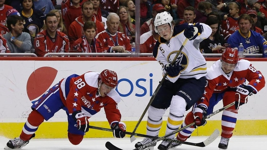 Washington Capitals defenseman Nate Schmidt (88) and center Jay Beagle (83) battle for control of the puck with Buffalo Sabres center Jack Eichel (15) during the first period of an NHL hockey game, Wednesday, Dec. 30, 2015, in Washington. (AP Photo/Carolyn Kaster)