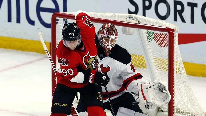 New Jersey Devils goaltender Cory Schneider (35) keeps eyes on the puck as he is screened by Ottawa Senators' Alex Chiasson (90) during the second period of an NHL hockey game Wednesday, Dec. 30, 2015, in Ottawa, Ontario. (Fred Chartrand/The Canadian Press via AP)