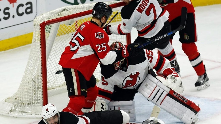 New Jersey Devils' David Schlemko (8) attempts to reach a loose puck as Devils goaltender Cory Schneider (35) and Ottawa Senators' Chris Neil (25) battle in front of the net during the first period of an NHL hockey game Wednesday, Dec. 30, 2015, in Ottawa, Ontario. (Fred Chartrand/The Canadian Press via AP)