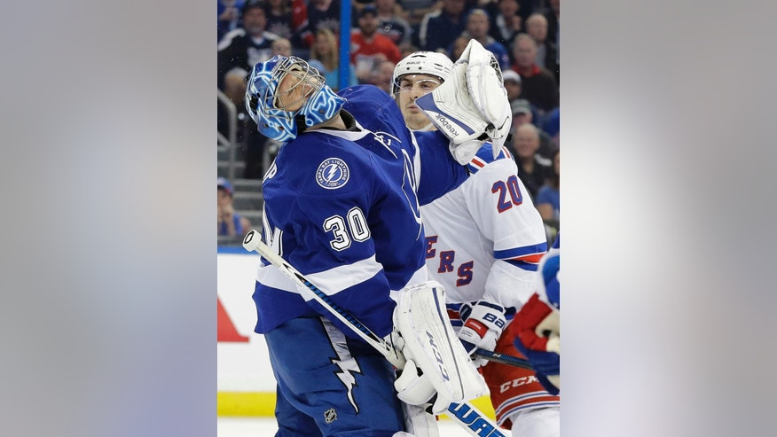 Tampa Bay Lightning goalie Ben Bishop (30) grimaces after getting hit with a high stick from New York Rangers left wing Chris Kreider (20) during the first period of an NHL hockey game Wednesday, Dec. 30, 2015, in Tampa, Fla. Kreider was penalized on the play. (AP Photo/Chris O'Meara)