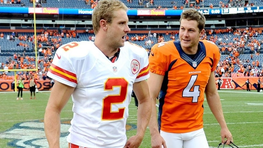 Sep 14, 2014; Denver, CO, USA; Kansas City Chiefs punter Dustin Colquitt (2) and Denver Broncos punter Britton Colquitt (4) talk following the game at Sports Authority Field at Mile High. The Broncos defeated the Chiefs 24-17. Mandatory Credit: Ron Chenoy-USA TODAY Sports