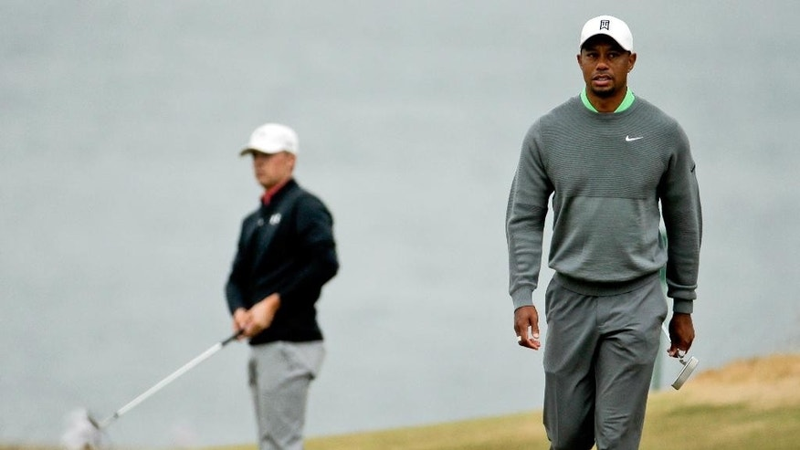 FILE - In this June 16, 1995, file photo, Tiger Woods, right, walks to the fifth green as Jordan Spieth chips during a practice round for the U.S. Open golf tournament at Chambers Bay in University Place, Wash. When Woods turned pro at 20, the No. 1 player in the world was 41-year-old Greg Norman. Woods is 40, and the No. 1 player is 22-year-old Spieth. (AP Photo/Charlie Riedel, File)