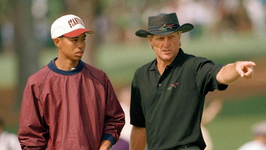 FILE - In this April 4, 1995, file photo, U.S. Amateur Champion Tiger Woods, left, talks with Greg Norman, of Australia, on the second hole during practice for the 1995 Masters golf tournament on the Augusta National Golf Club in Augusta, Ga. When Woods turned pro at 20, the No. 1 player in the world was 41-year-old Greg Norman. Woods is 40, and the No. 1 player is 22-year-old Spieth. (AP Photo/Dave Martin, File)