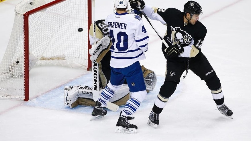 Toronto Maple Leafs' Michael Grabner (40) screens Pittsburgh Penguins goalie Matt Murray (30) with Penguins' Ben Lovejoy (12) defending as a goal by Dion Phaneuf bounces out of the net during the first period of an NHL hockey game in Pittsburgh, Wednesday, Dec. 30, 2015. (AP Photo/Gene J. Puskar)