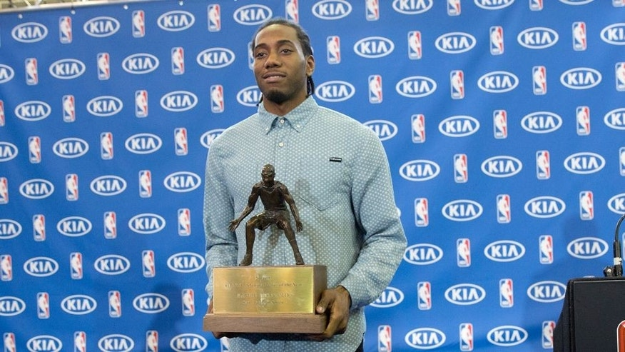 San Antonio Spurs' Kawhi Leonard holds his trophy during a news conference after he was named the NBA defensive player of the year, Thursday, April 23, 2015, in San Antonio. (AP Photo/Eric Gay)
