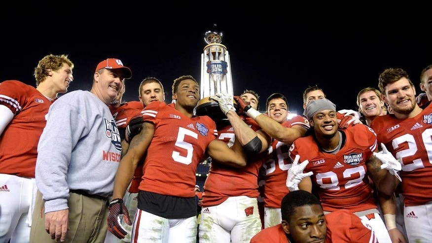 Dec 30, 2015; San Diego, CA, USA;Wisconsin Badgers players and head coach Paul Chryst hoist the championship trophy after the 2015 Holiday Bowl against the Southern California Trojans at Qualcomm Stadium. Wisconsin defeated USC 23-21. Mandatory Credit: Kirby Lee-USA TODAY Sports