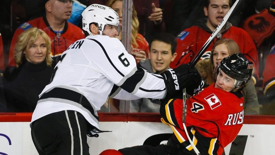 Los Angeles Kings' Jake Muzzin, left, checks Calgary Flames' Kris Russell during the third period of an NHL hockey game in Calgary, Alberta on Thursday, Dec. 31, 2015. (Jeff McIntosh/The Canadian Press via AP) MANDATORY CREDIT