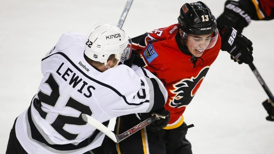 Los Angeles Kings' Trevor Lewis, left, is checked by Calgary Flames' Johnny Gaudreau during the third period of an NHL hockey game in Calgary, Alberta on Thursday, Dec. 31, 2015. (Jeff McIntosh/The Canadian Press via AP) MANDATORY CREDIT