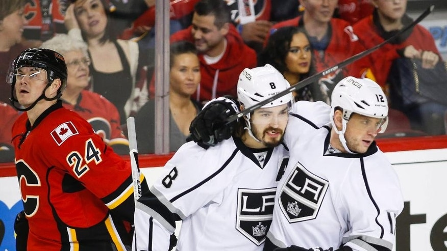 Los Angeles Kings' Marian Gaborik, right, of Slovakia, celebrates his goal with teammate Drew Doughty, center, as Calgary Flames' Jiri Hudler, from the Czech Republic, skates away during first-period NHL hockey game action in Calgary, Alberta, Thursday, Dec. 31, 2015. (Jeff McIntosh/The Canadian Press via AP) MANDATORY CREDIT