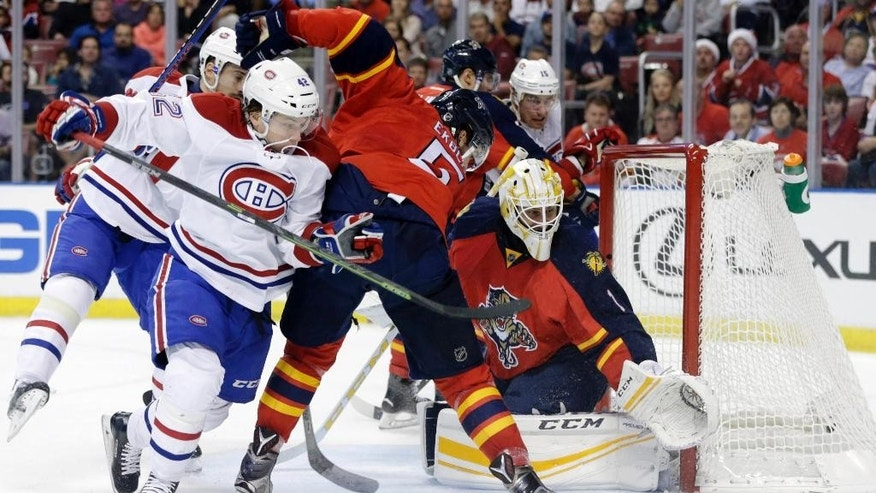 Florida Panthers goalie Roberto Luongo, right, makes a save as Montreal Canadiens right wing Sven Andrighetto (42) eyes the puck during the first period of an NHL hockey game, Tuesday, Dec. 29, 2015, in Sunrise, Fla. (AP Photo/Lynne Sladky)
