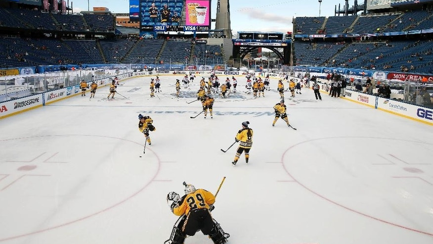 The Boston Pride, foreground, warm up before a women's outdoor hockey game against the Montreal Les Canadiennes at Gillette Stadium in Foxborough, Mass., Thursday, Dec. 31, 2015, where the Boston Bruins will play the Montreal Canadiens in the NHL Winter Classic on Friday. (AP Photo/Michael Dwyer)