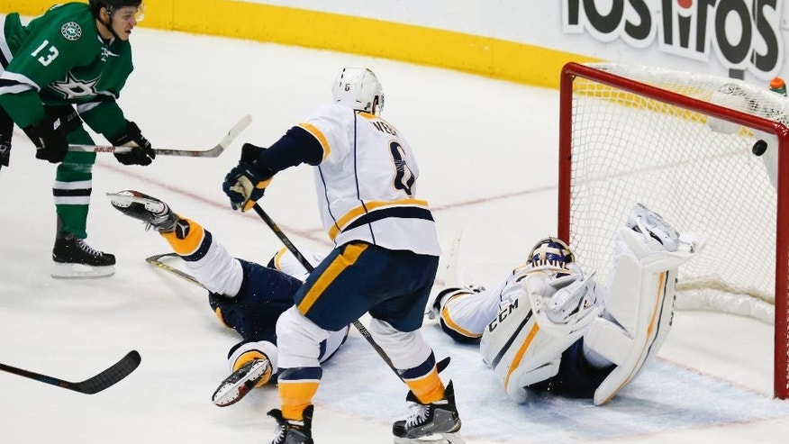 Dallas Stars center Mattias Janmark (13) watches his shot on goal slip by Nashville Predators goalie Pekka Rinne during the second period of an NHL hockey game, Thursday, Dec. 31, 2015, in Dallas. (AP Photo/Jim Cowsert)