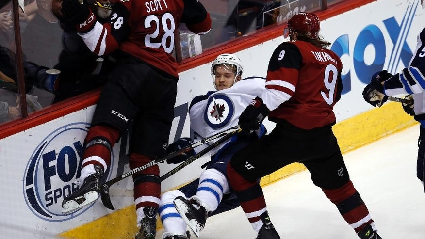 Arizona Coyotes left wings John Scott (28) and Viktor Tikhonov (9) check Winnipeg Jets right wing Joel Armia, center, in the second period during an NHL hockey game, Thursday, Dec. 31, 2015, in Glendale, Ariz. (AP Photo/Rick Scuteri)