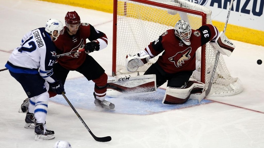 Arizona Coyotes goalie Louis Domingue (35) makes the save against Winnipeg Jets right wing Drew Stafford (12) in the second period during an NHL hockey game, Thursday, Dec. 31, 2015, in Glendale, Ariz. (AP Photo/Rick Scuteri)
