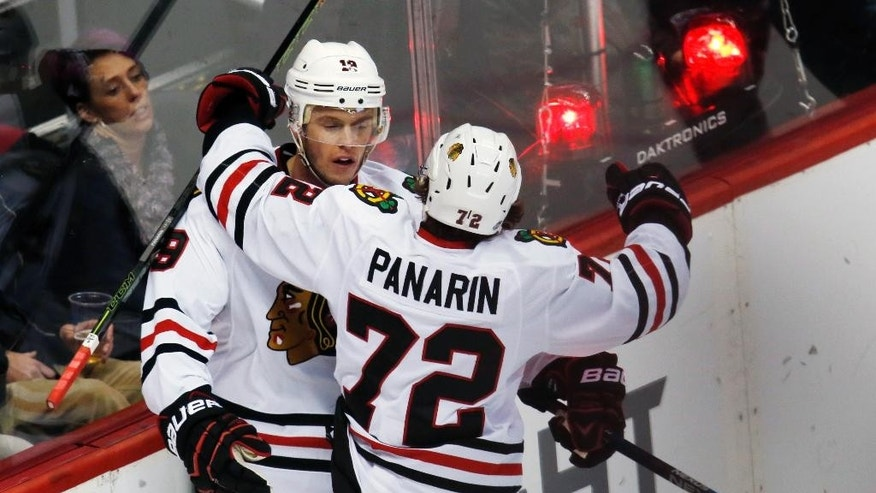 Chicago Blackhawks center Jonathan Toews, left, celebrates after scoring the winning goal with left wing Artemi Panarin, of Russia, against the Colorado Avalanche in overtime of an NHL hockey game Thursday, Dec. 31, 2015, in Denver. Chicago won 4-3. (AP Photo/David Zalubowski)