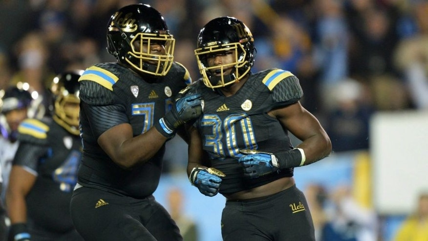 <p>UCLA Bruins running back Myles Jack (30) celebrates with offensive lineman Caleb Benenoch (74) after scoring on a 2-yard touchdown run in the third quarter for his fourth touchdown against the Washington Huskies at Rose Bowl. Mandatory Credit: Kirby Lee-USA TODAY Sports</p>