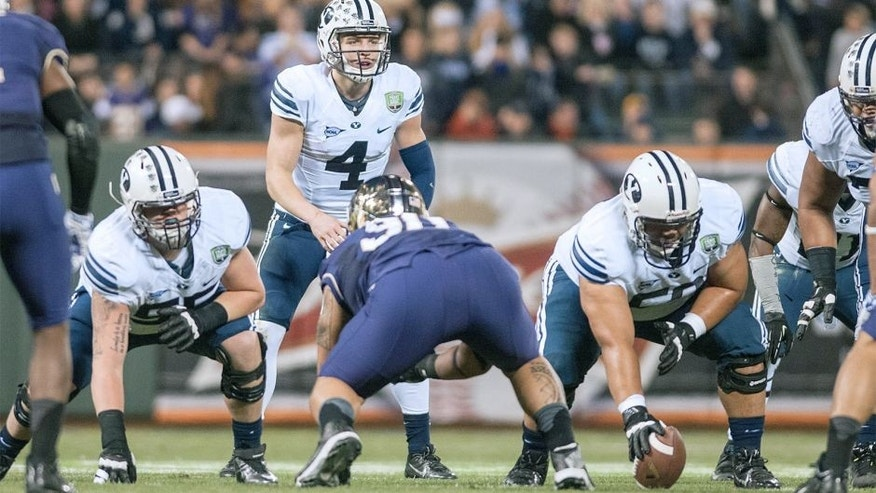 Dec 27, 2013; San Francisco, CA, USA; Brigham Young Cougars quarterback Taysom Hill (4) prepares to hike the ball against the Washington Huskies during the second quarter at AT&T Park. Mandatory Credit: Ed Szczepanski-USA TODAY Sports