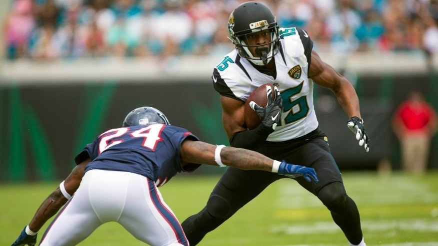 Oct 18, 2015; Jacksonville, FL, USA; Jacksonville Jaguars wide receiver Allen Robinson (15) catches a pass as Houston Texans cornerback Johnathan Joseph (24) goes for a tackle in the second quarter at EverBank Field. Mandatory Credit: Logan Bowles-USA TODAY Sports