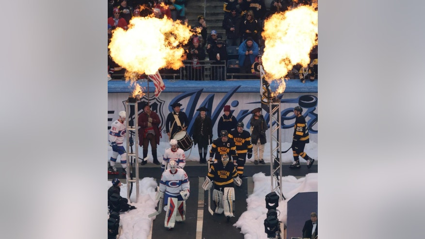 Flame towers ignite as the Montreal Canadiens, left, and Boston Bruins, right, file towards the ice prior to the NHL Winter Classic hockey game at Gillette Stadium in Foxborough, Mass., Friday, Jan. 1, 2016. (AP Photo/Charles Krupa)