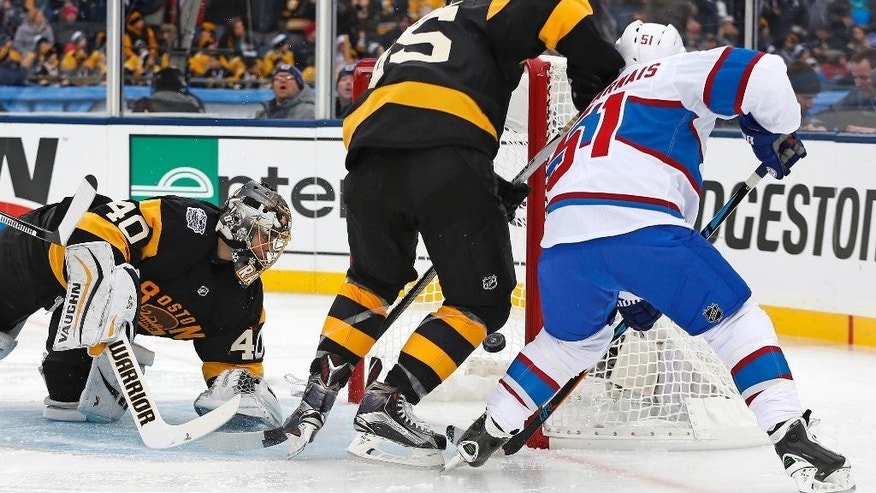 Montreal Canadiens center David Desharnais (51) pokes the puck past Boston Bruins goalie Tuukka Rask (40) for a goal during the first period of the NHL Winter Classic hockey game at Gillette Stadium in Foxborough, Mass., Friday, Jan. 1, 2016. At center is Bruins defenseman Joe Morrow (45). (AP Photo/Michael Dwyer)