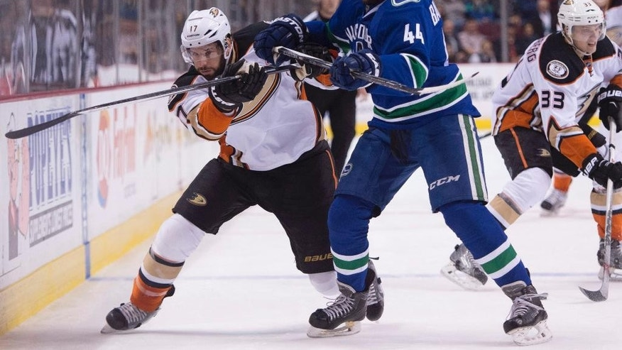 Vancouver Canucks defenseman Matt Bartkowski (44) fights for control of the puck with Anaheim Ducks' Ryan Kesler (17) during the first period of an NHL hockey game in Vancouver, British Columbia, Friday, Jan. 1, 2016.  (Jonathan Hayward/The Canadian Press via AP) MANDATORY CREDIT