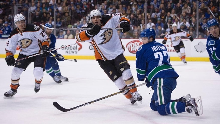 Anaheim Ducks center Mike Santorelli (25) tries to get a shot past Vancouver Canucks defenseman Ben Hutton (27) as Anaheim Ducks center Shawn Horcoff (22) looks on during the first period of an NHL hockey game in Vancouver, British Columbia, Friday, Jan. 1, 2016.  (Jonathan Hayward/The Canadian Press via AP) MANDATORY CREDIT