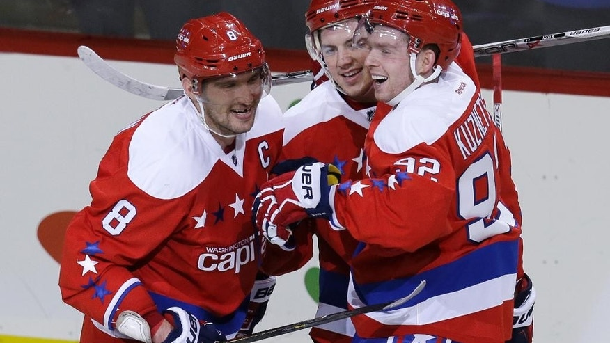 Washington Capitals left wing Alex Ovechkin (8) celebrates scoring an empty net goal with teammates T.J. Oshie (77), and Evgeny Kuznetsov (92) during the third period of an NHL hockey game against Buffalo Sabres, Wednesday, Dec. 30, 2015, in Washington. Ovechkin scored two goals in the Capitals 5-2 victory. (AP Photo/Carolyn Kaster)