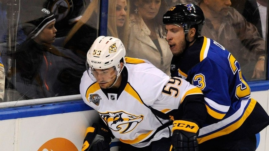 Nashville Predators' Roman Josi (59), of Switzerland, reaches for the puck with St. Louis Blues' Jordan Caron (33) during the first period of an NHL hockey game, Tuesday, Dec. 29, 2015, in St. Louis. The Blues won in overtime 4-3. (AP Photo/Bill Boyce)