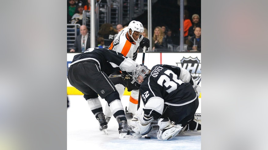 Los Angeles Kings goalie Jonathan Quick, right, stops a shot by Philadelphia Flyers' Wayne Simmonds, center, during the first period of an NHL hockey game, Saturday, Jan. 2, 2016, in Los Angeles. Kings' Brayden McNabb, left, is in on the play. (AP Photo/Jae C. Hong)