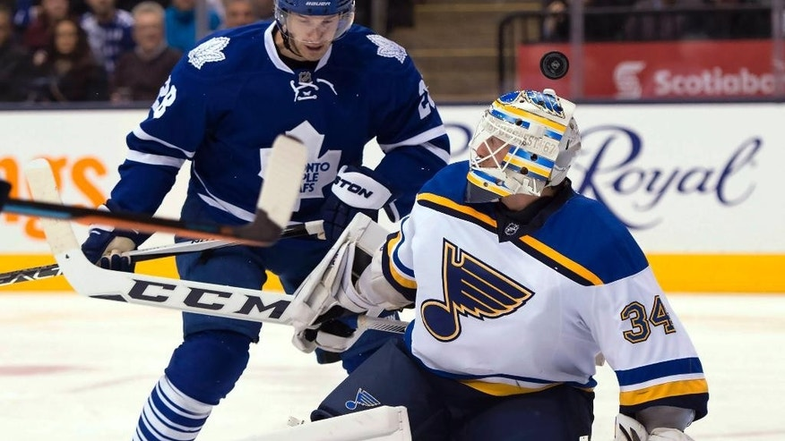 St. Louis Blues goaltender Jake Allen loses track of the puck over his head under pressure from Toronto Maple Leafs right winger Brad Boyes (28) during the second period of an NHL hockey game in Toronto on Saturday, Jan. 2, 2016. (Frank Gunn/The Canadian Press via AP)