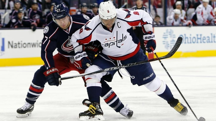 Washington Capitals' Alex Ovechkin, right, of Russia, carries the puck up ice as Columbus Blue Jackets' Ryan Murray defends during the first period of an NHL hockey game Saturday, Jan. 2, 2016, in Columbus, Ohio. (AP Photo/Jay LaPrete)