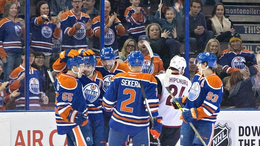 Arizona Coyotes' Kyle Chipchura (24) skates past as the Edmonton Oilers celebrate a goal during first period NHL action in Edmonton, on Saturday, Jan. 2, 2016. (Jason Franson/The Canadian Press via AP)