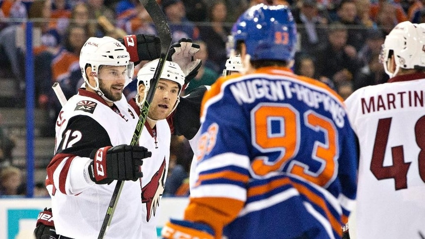 Arizona Coyotes' Brad Richardson (12) and Steve Downie (17) celebrate a goal against the Edmonton Oilers during first period NHL action in Edmonton, on Saturday, Jan. 2, 2016. (Jason Franson/The Canadian Press via AP)
