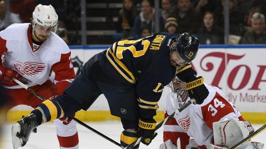 Buffalo Sabres right winger Brian Gionta (12) reaches back for the puck as Detroit Red Wings defenseman Brendan Smith (2) and goaltender Petr Mrazek (34), of the Czech Republic, defend during the first period of an NHL hockey game, Saturday Jan. 2, 2016 in Buffalo, N.Y. (AP Photo/Gary Wiepert)