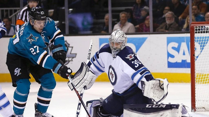 Winnipeg Jets goalie Connor Hellebuyck (30) blocks a shot by San Jose Sharks' Joonas Donskoi (27) during the first period of an NHL hockey game Saturday, Jan. 2, 2016, in San Jose, Calif. (AP Photo/Tony Avelar)