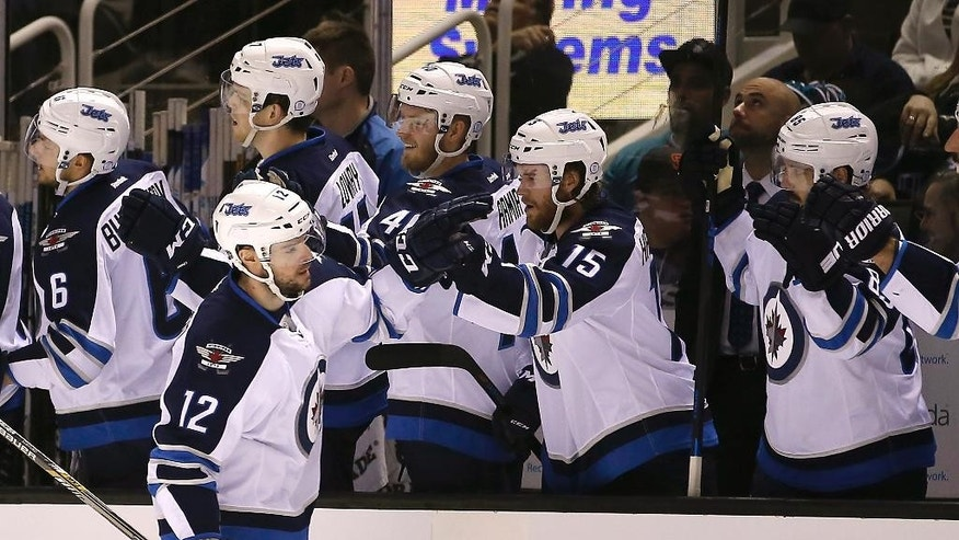 Winnipeg Jets' Drew Stafford (12) is congratulated after scoring against the San Jose Sharks during the first period of an NHL hockey game Saturday, Jan. 2, 2016, in San Jose, Calif. (AP Photo/Tony Avelar)