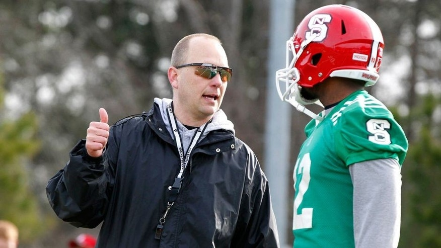 N.C. State Wolfpack offensive coordinator Matt Canada talks with Jacoby Brissett (12) during spring football practice in Raleigh, N.C., on Wednesday, March 5, 2014. (Ethan Hyman/Raleigh News & Observer/MCT)