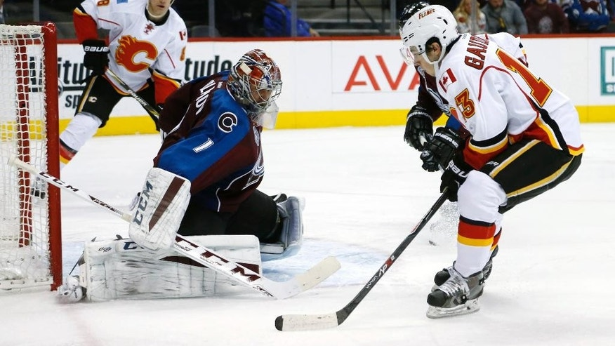 Calgary Flames left wing Johnny Gaudreau, right, looks to shot on Colorado Avalanche goalie Semyon Varlamov, of Russia, in second period of an NHL hockey game Saturday, Jan. 2, 2016, in Denver. (AP Photo/David Zalubowski)