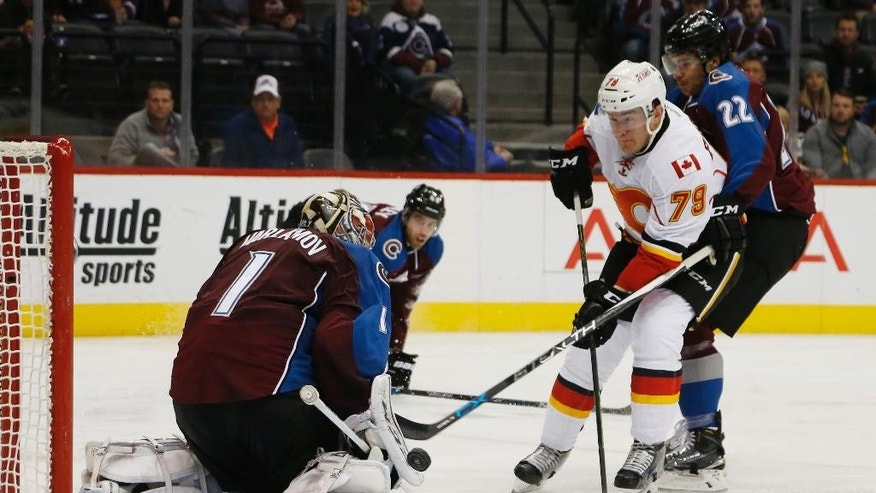 Colorado Avalanche goalie Semyon Varlamov, left, of Russia, stops shot off stick of Calgary Flames left wing Micheal Ferland, center, as Avalanche defenseman Zach Redmond covers in second period of an NHL hockey game Saturday, Jan. 2, 2016, in Denver. (AP Photo/David Zalubowski)