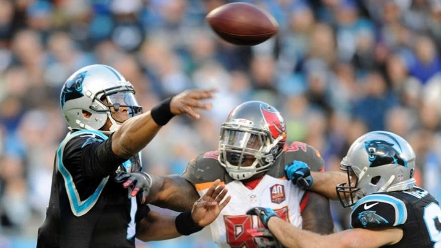 Carolina Panthers quarterback Cam Newton, left, throws a pass under pressure from Tampa Bay Buccaneers defensive end Howard Jones, right, in the first half of an NFL football game in Charlotte, N.C., Sunday, Jan. 3, 2016. (AP Photo/Mike McCarn)