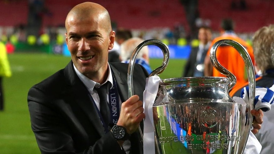 FILE - In this May 24, 2014 file photo, former player and current Real Madrid B team coach Zinedine Zidane lifts the Champion League trophy, at the end of the Champions League final soccer match between Atletico Madrid and Real Madrid in Lisbon, Portugal. Real Madrid's President Florentino Perez announced Monday Jan. 4, 2016 that current coach Rafael Benitez has been fired and former player and Real Madrid's B team coach Zinedine Zidane will take over. Benitez, hired seven months ago, has been under pressure since a demoralizing 4-0 home loss to Barcelona in November. (AP Photo/Andres Kudacki, File)