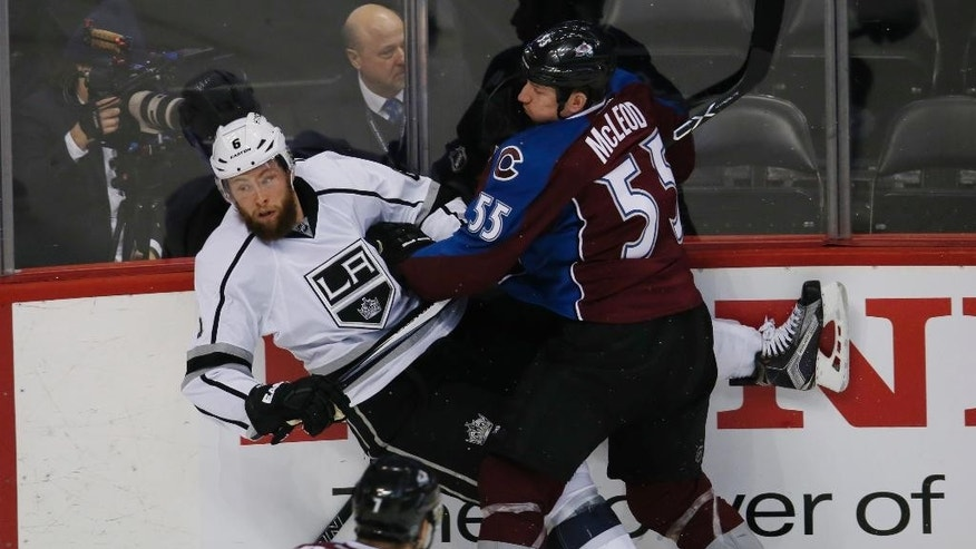 Colorado Avalanche left wing Cody McLeod, back, right, knocks Los Angeles Kings defenseman Jake Muzzin,left, of his skates with a check as Avalanche center John Mitchell, front, looks on in the first period of an NHL hockey game Monday, Jan. 4, 2016, in Denver. (AP Photo/David Zalubowski)