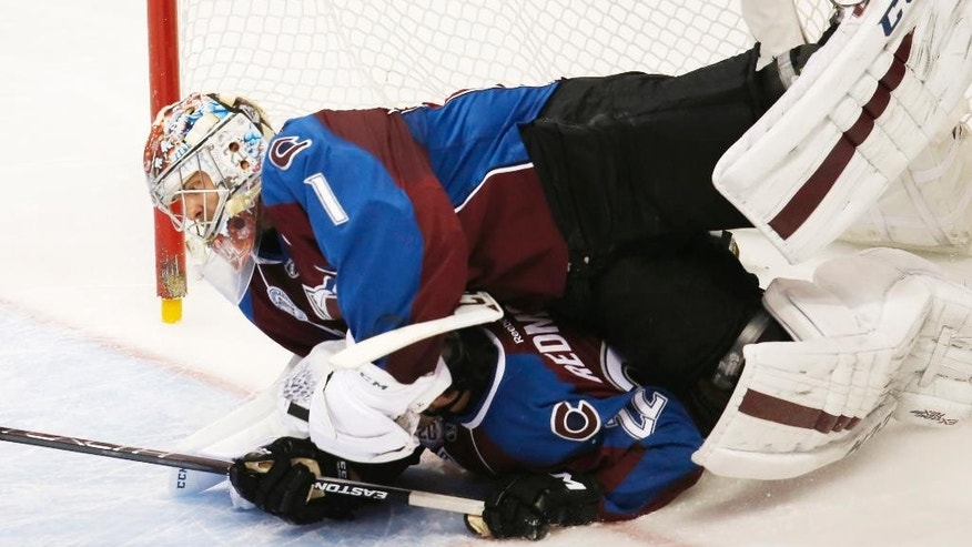 Colorado Avalanche goalie Semyon Varlamov, top, of Russia, is knocked off his skates by defenseman Zach Redmond after he was knocked over by Los Angeles Kings left wing Dwight King in the first period of an NHL hockey game Monday, Jan. 4, 2016, in Denver. (AP Photo/David Zalubowski)