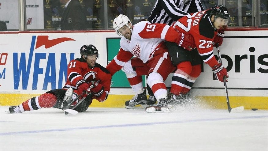 Detroit Red Wings center Riley Sheahan, center, is caught between New Jersey Devils center Stephen Gionta, left, and right winger Jordin Tootoo, right, during the first period of an NHL hockey game Monday, Jan. 4, 2016, in Newark, N.J. (AP Photo/Mel Evans)