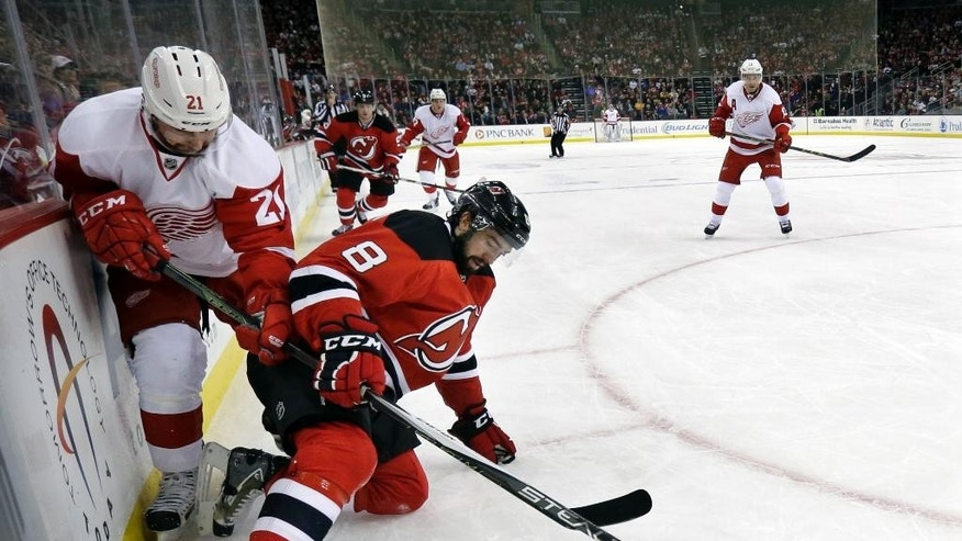 Detroit Red Wings left winger Tomas Tatar, left, of Slovakia, and New Jersey Devils defenseman David Schlemko, right, collide over the puck during the first period of an NHL hockey game Monday, Jan. 4, 2016, in Newark, N.J. (AP Photo/Mel Evans)