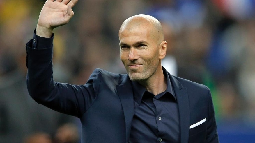 FILE - In this March 26, 2015 file photo, former soccer player and current Real Madrid B team coach Zinedine Zidane waves to spectators prior to the international friendly soccer match between France and Brazil at the Stade de France, north of Paris, France. Real Madrid's President Florentino Perez announced Monday Jan. 4, 2016 that current coach Rafael Benitez has been fired and former player and Real Madrid's B team coach Zinedine Zidane will take over. Benitez, hired seven months ago, has been under pressure since a demoralising 4-0 home loss to Barcelona in November. The team won seven of nine matches since the defeat at the Bernabeu, but fans continued to call for Benitez's departure. (AP Photo/Francois Mori, File)