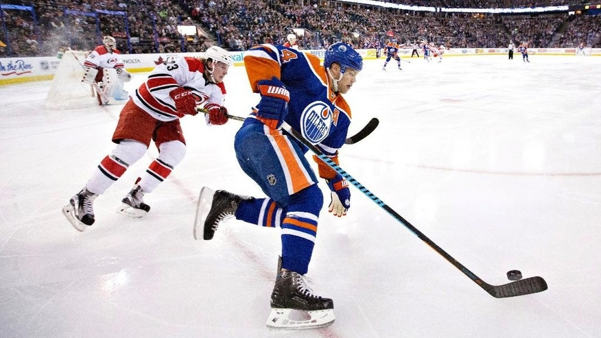 Carolina Hurricanes' Brock McGinn, left, chases Edmonton Oilers' Taylor Hall, right, during second period NHL action in Edmonton, Alberta, Monday, Jan. 4, 2016. (Jason Franson/The Canadian Press via AP)